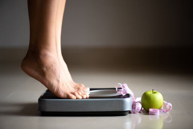 female-leg-stepping-weigh-scales-with-measuring-tape-apple_53476-4004